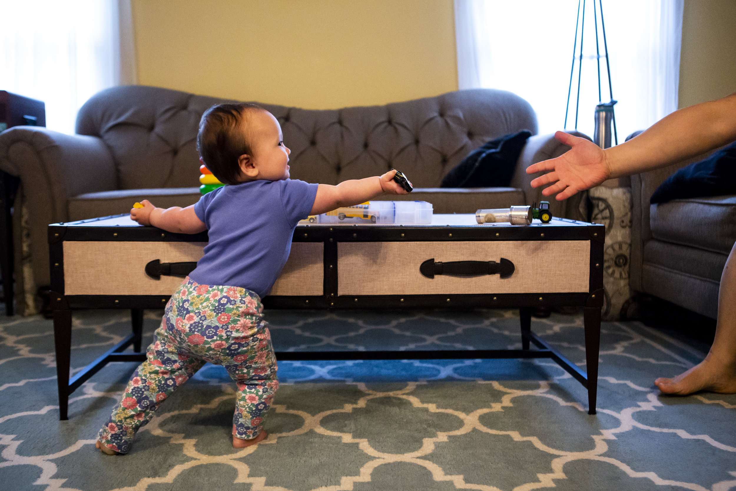 Toddler stretches to pass dad the remote control