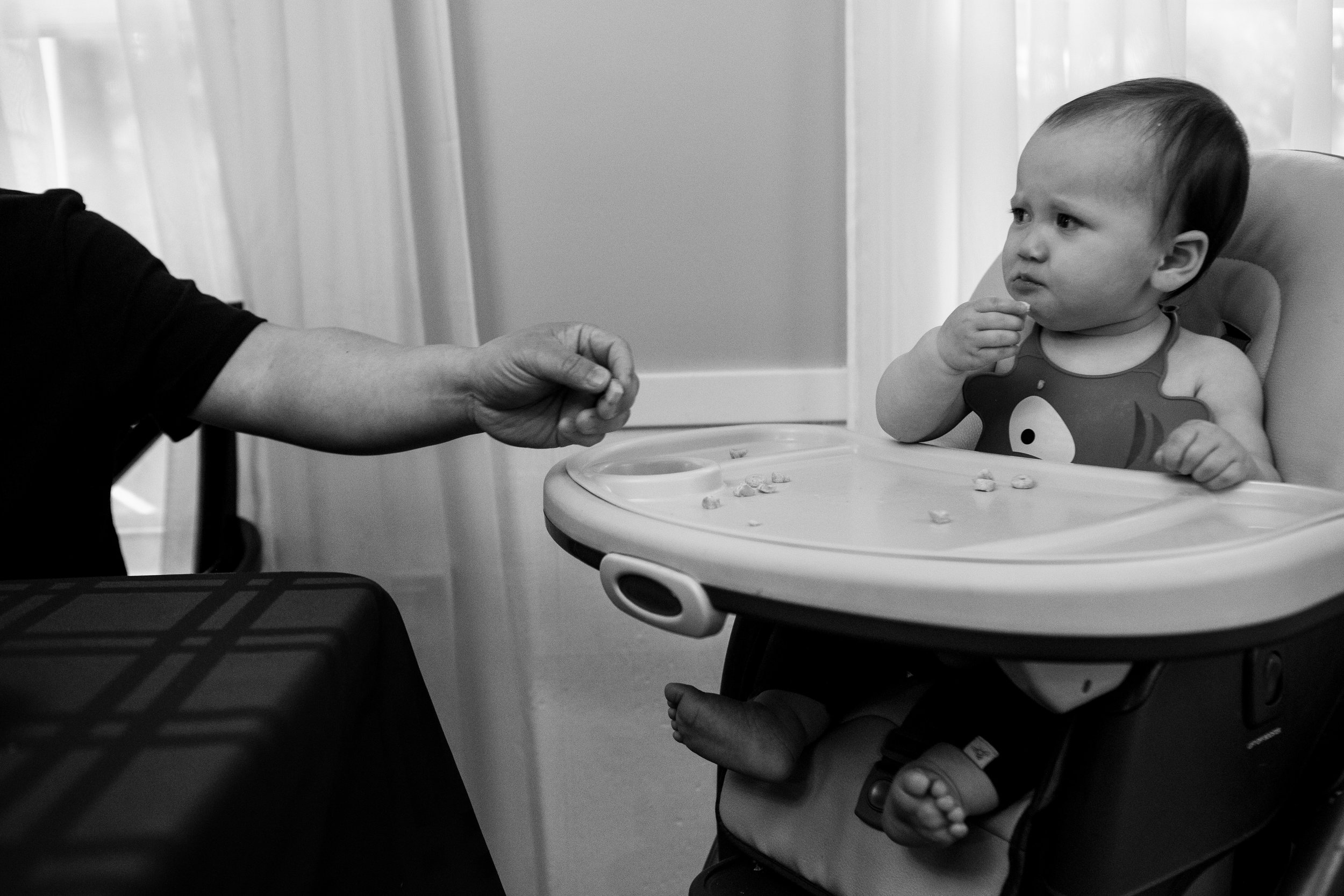 Family storytelling photography in black and white with a picky looking toddler and dad handing her food.