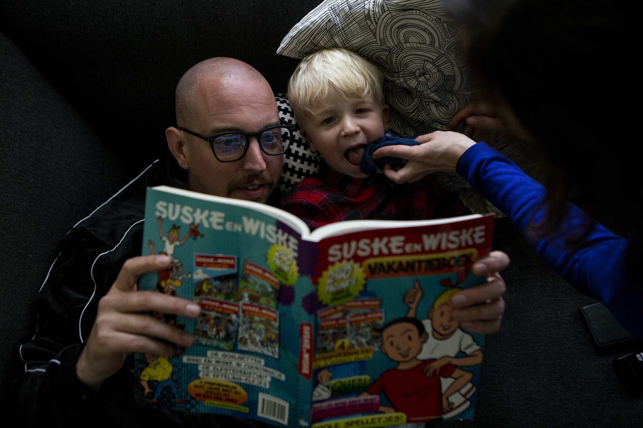 Real life Boston family portrait of father and son reading a comic and mom wiping sons face.