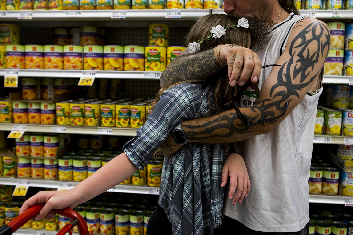 Award-winning Boston family photograph of father hugging daughter in supermarket in front of canned fruit.
