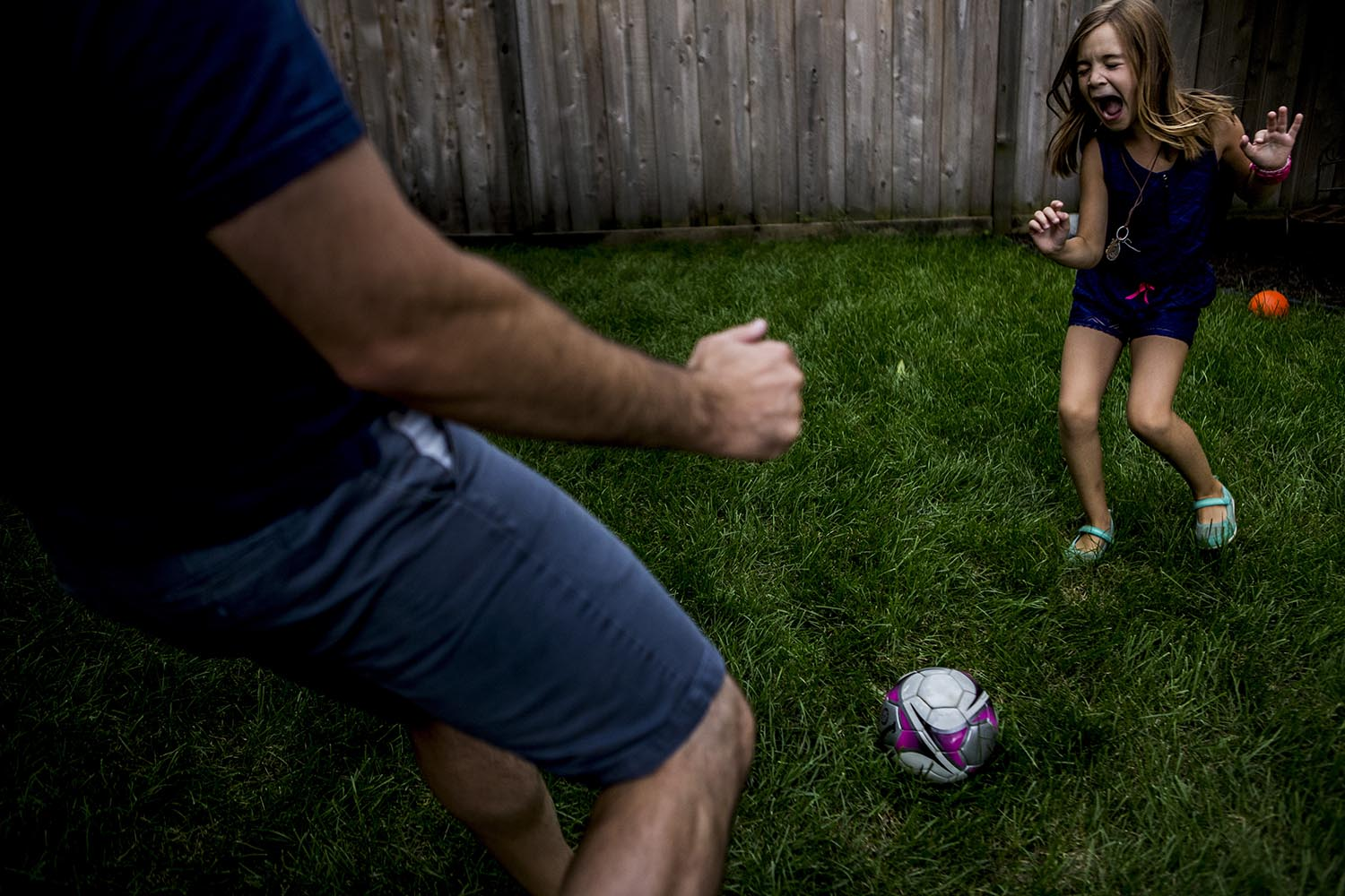 great action shot of boston daughter playing soccer with her dad