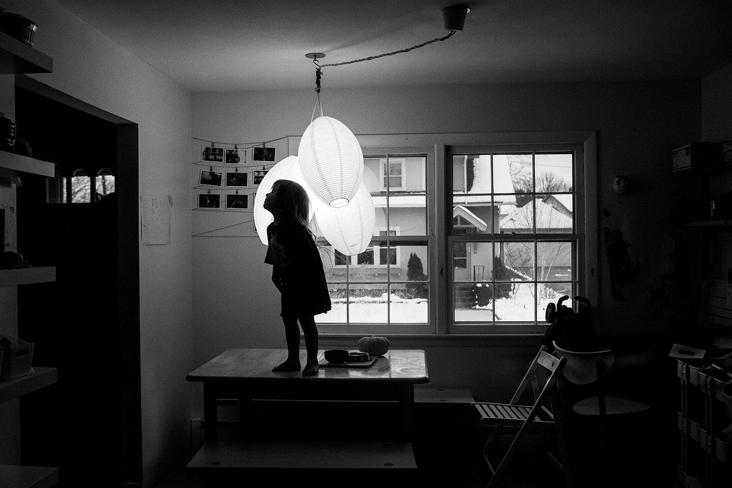 thoughtful black and white child portraiture of boston kid standing on the kitchen table in sillohuette