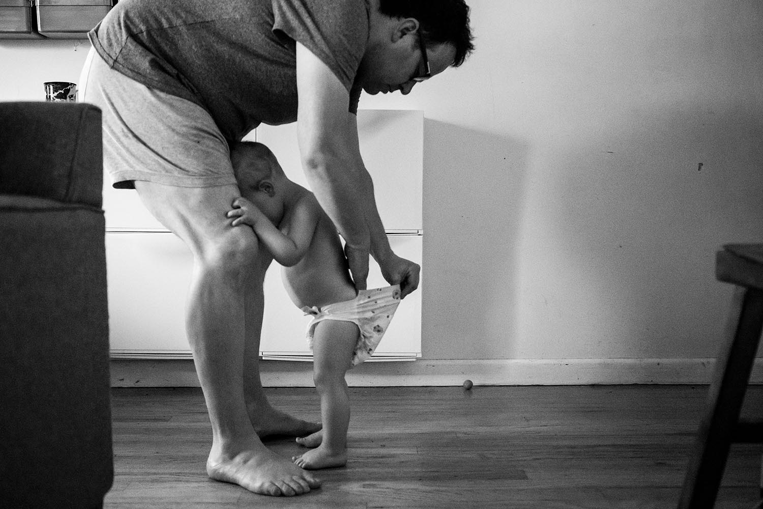 funny portrait of fatherhood in boston with dad checking toddler diaper for poop