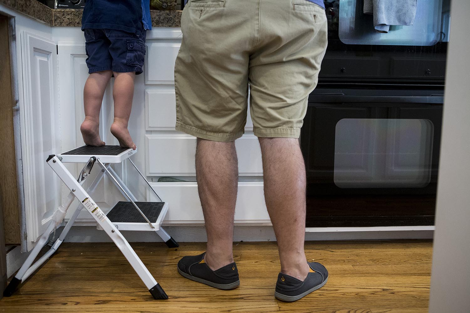 Candid father and son moment, picture of father and son's legs in the kitchen in Belmont MA the son is on tip toes on a stool