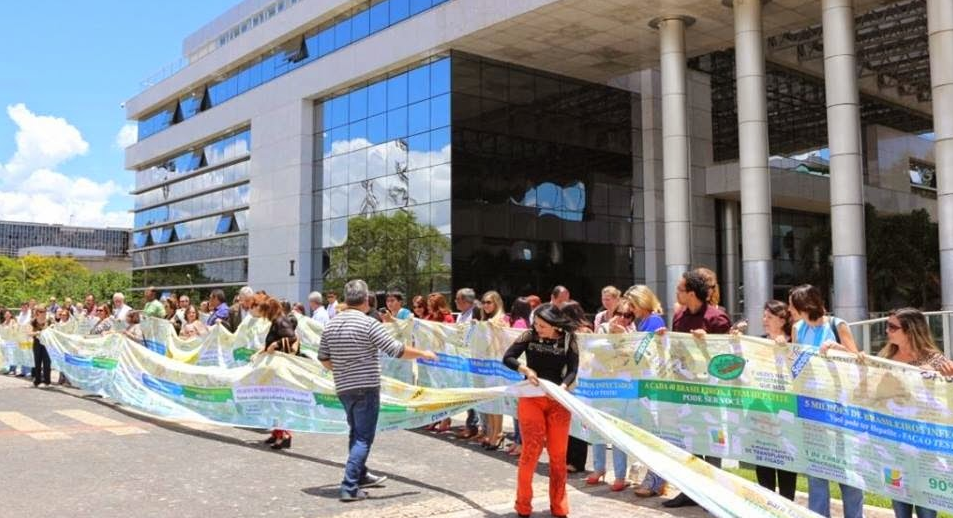 Pessoas de movimentos de enfrentamento às hepatites virais fazem abraço simbólico no Ministério da Saúde. (foto: Arquivo pessoal)