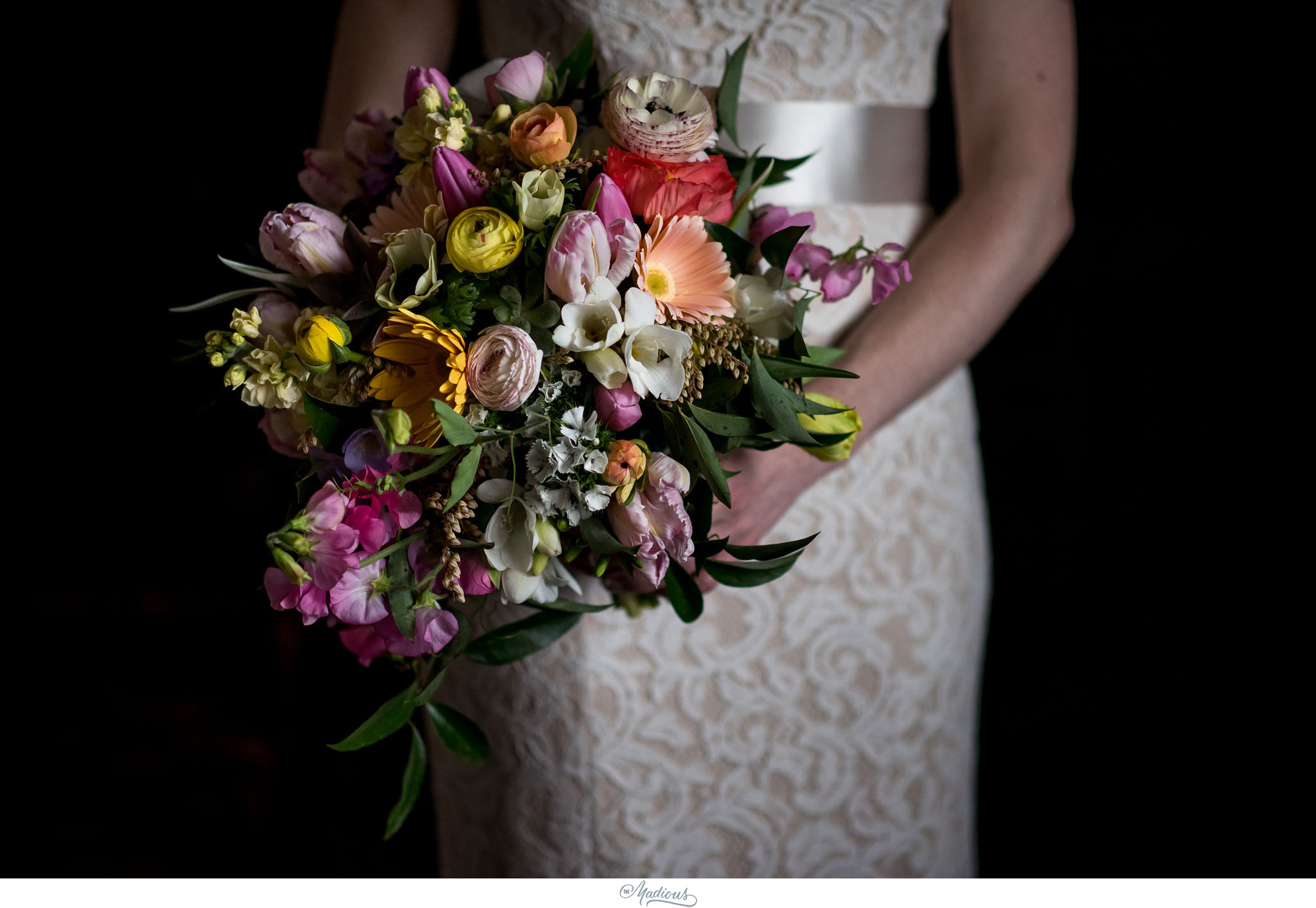 Local bouquet by   Local Color Flowers   including ranunculus, tulips, anemones, peonies, gerbera daisies, curly willow. Photo by   The Madious