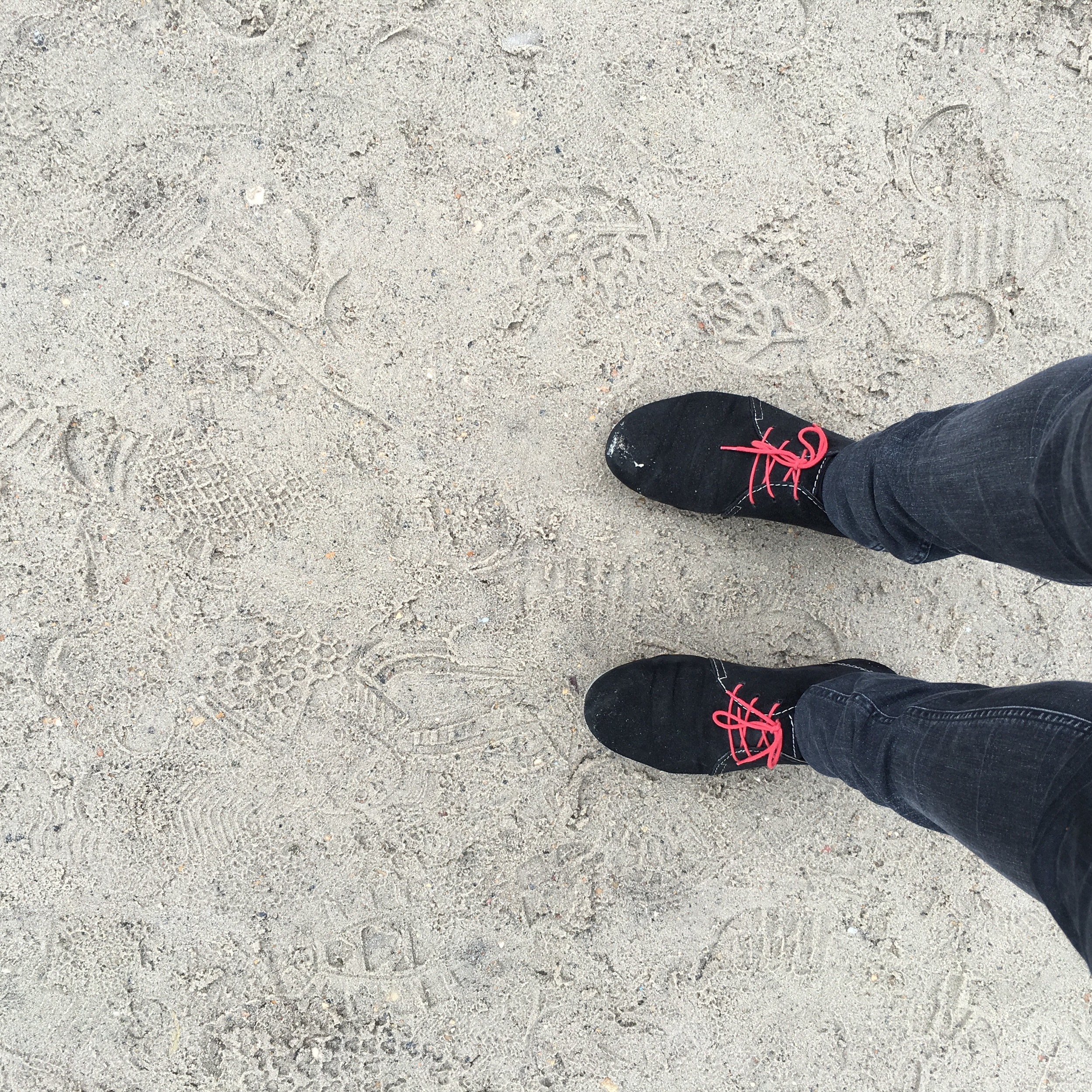 Black suede shoes on wet sand
