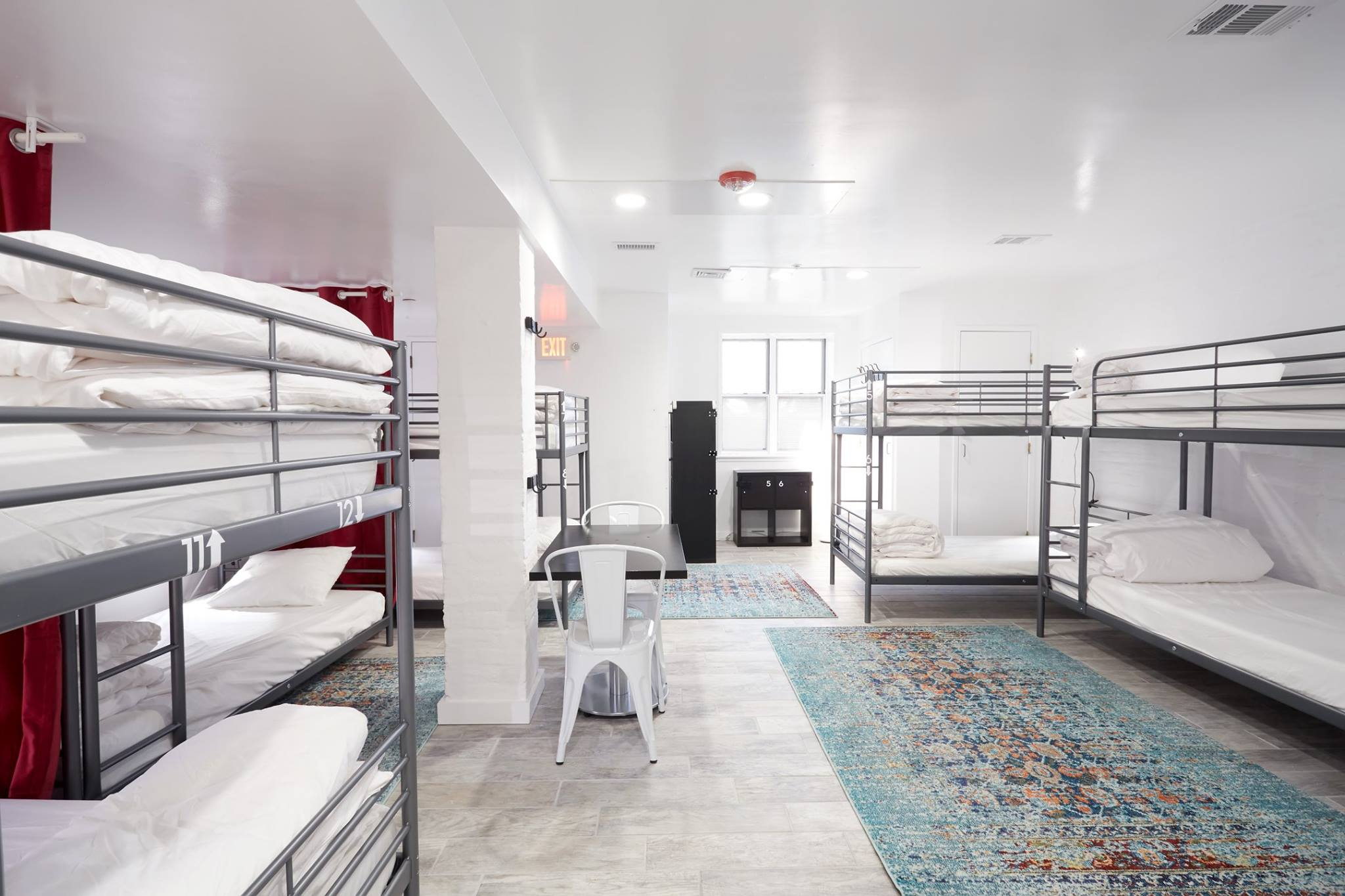 Bunk beds arranged in a clean bright backpackers dorm room