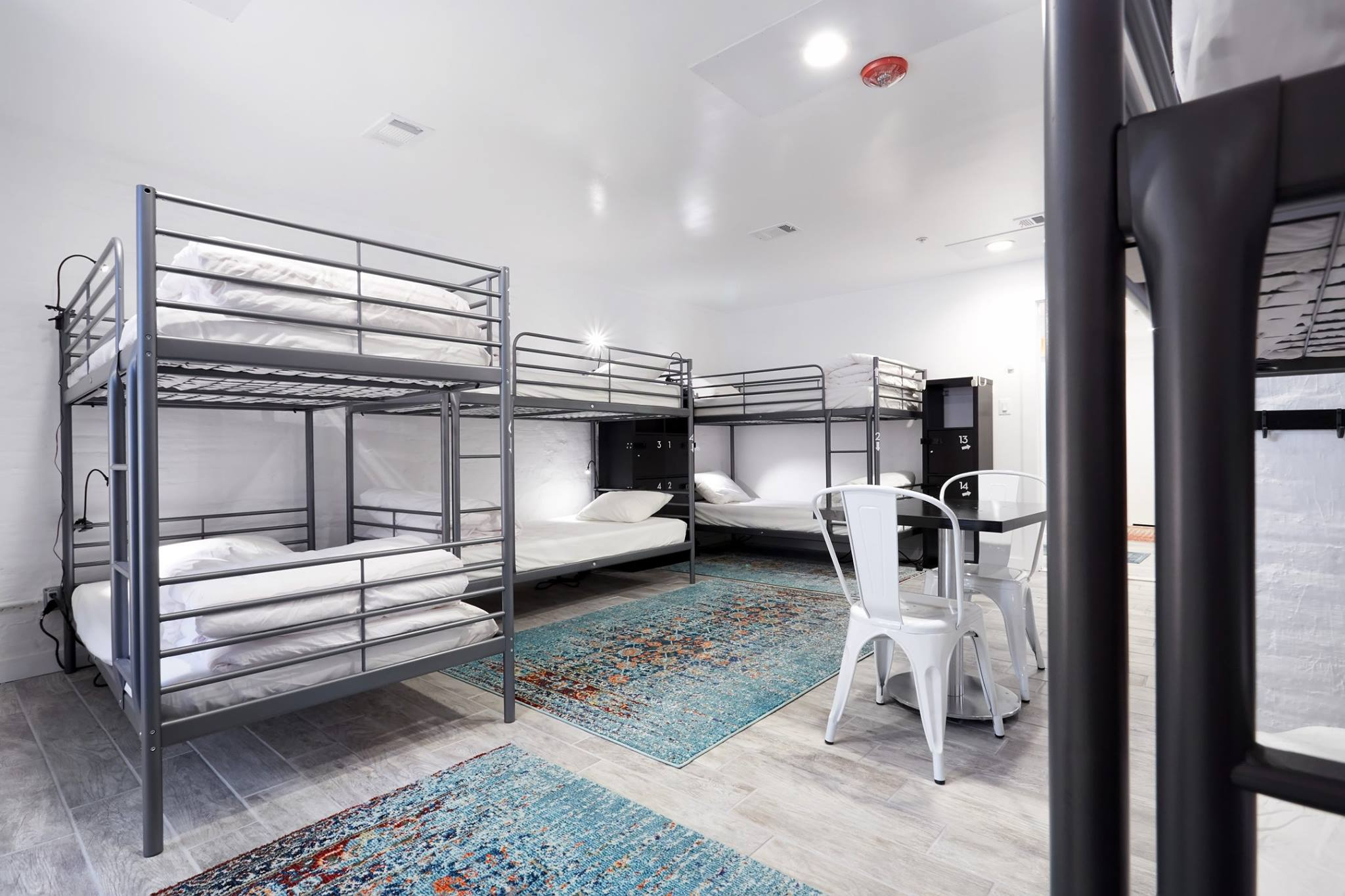 Bunk beds arranged in a bright backpackers dorm room
