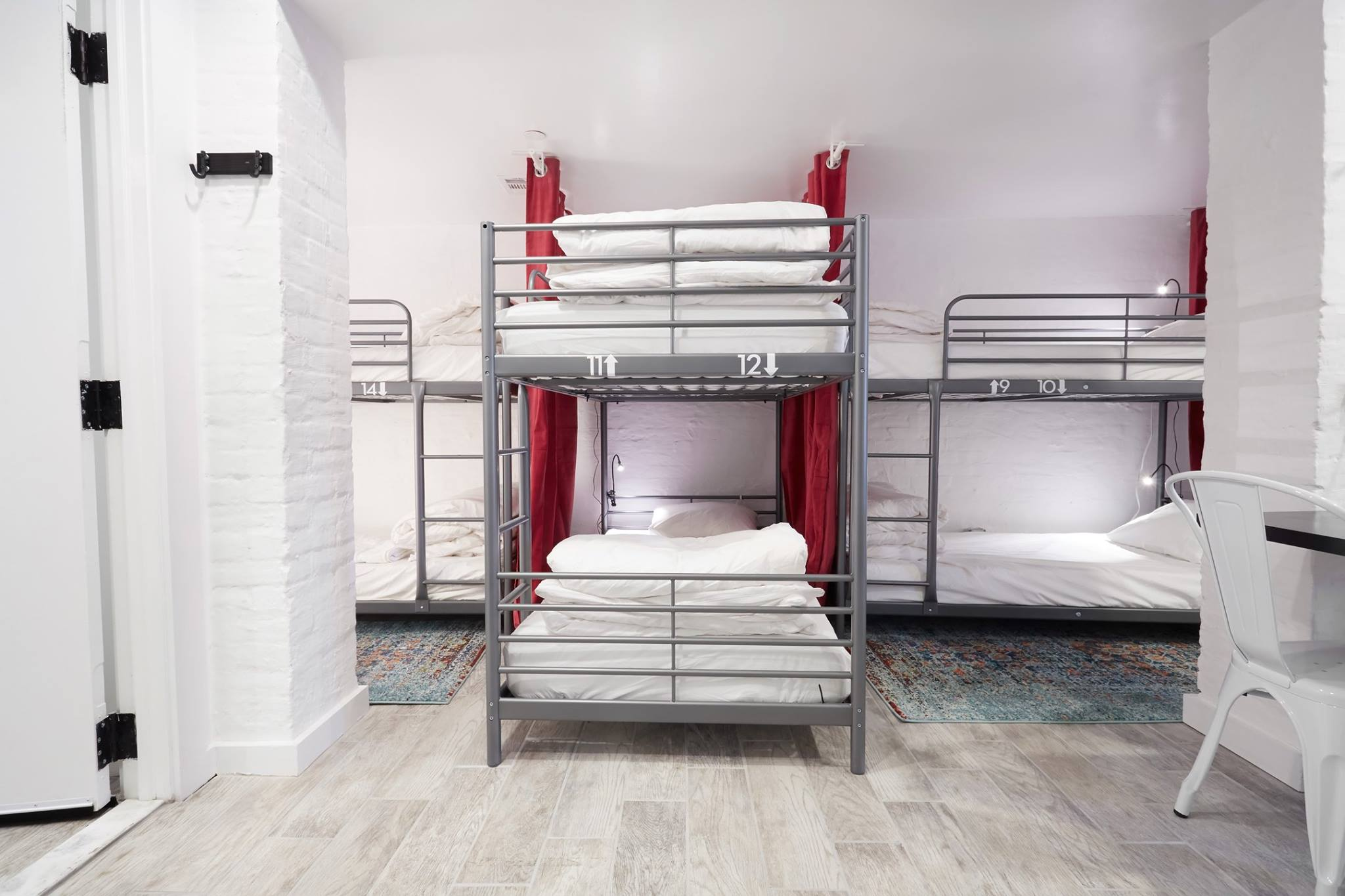 Straight on view of bunk beds and tile floor in backpackers dorm room