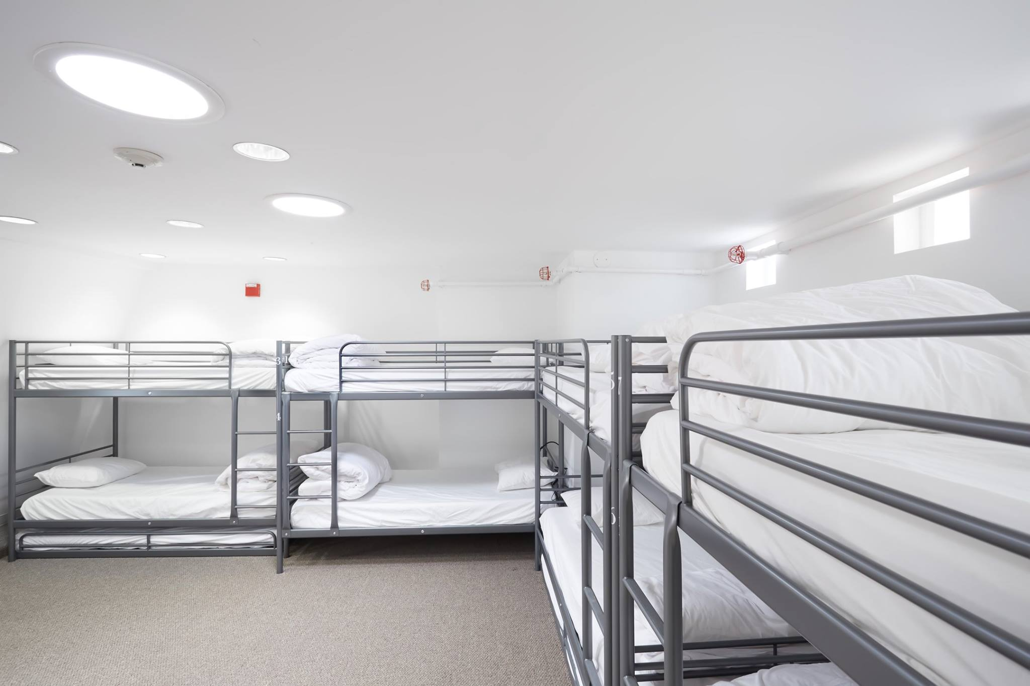 Bunk beds with clean linens arranged in a shared room