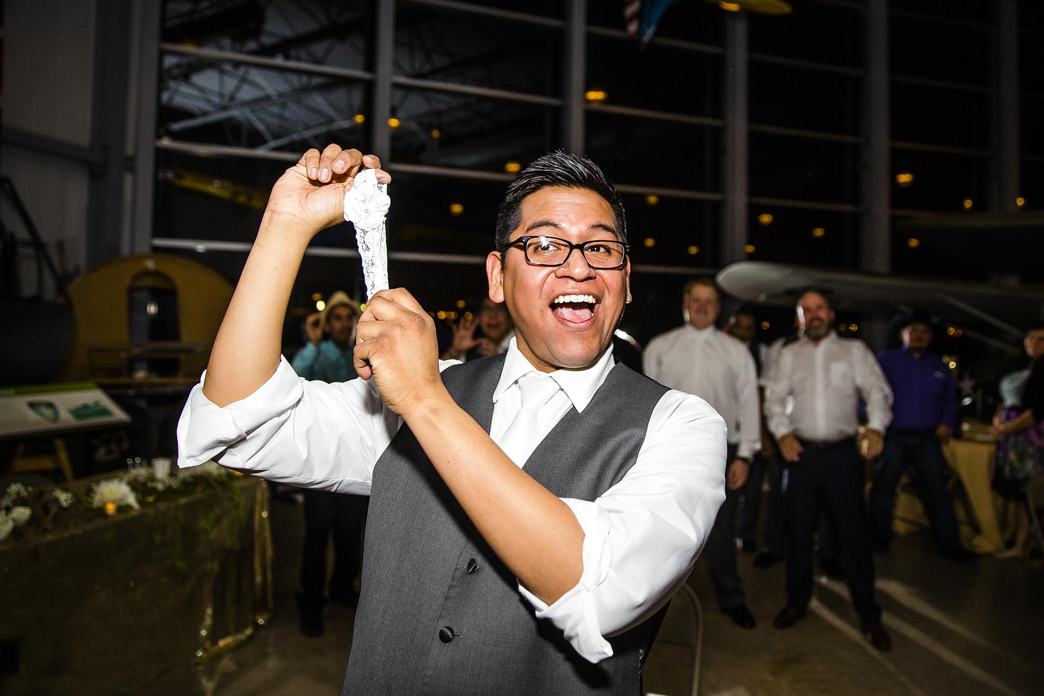 garter toss, groom, fun wedding reception, dramatic, edgy