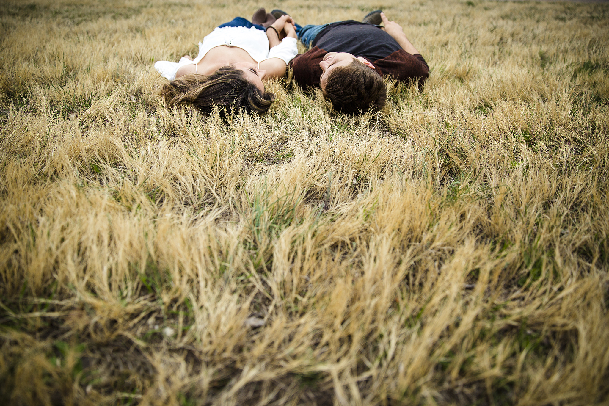laying in the grass, romantic, holding hands, creative engagement photography