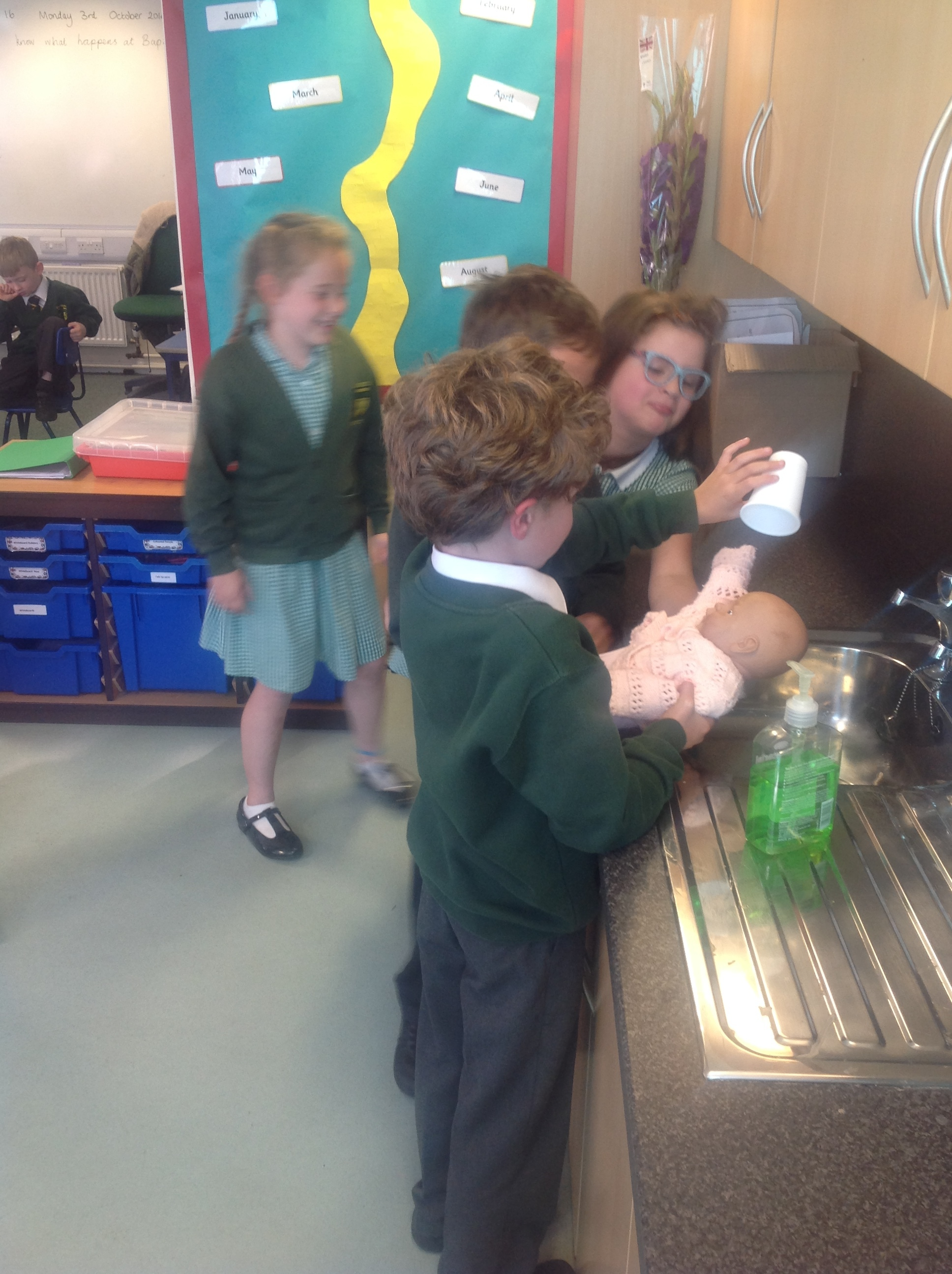 The baby is baptised with holy water as it is poured over their head three times, at the baptismal font (Year 3 sink!)