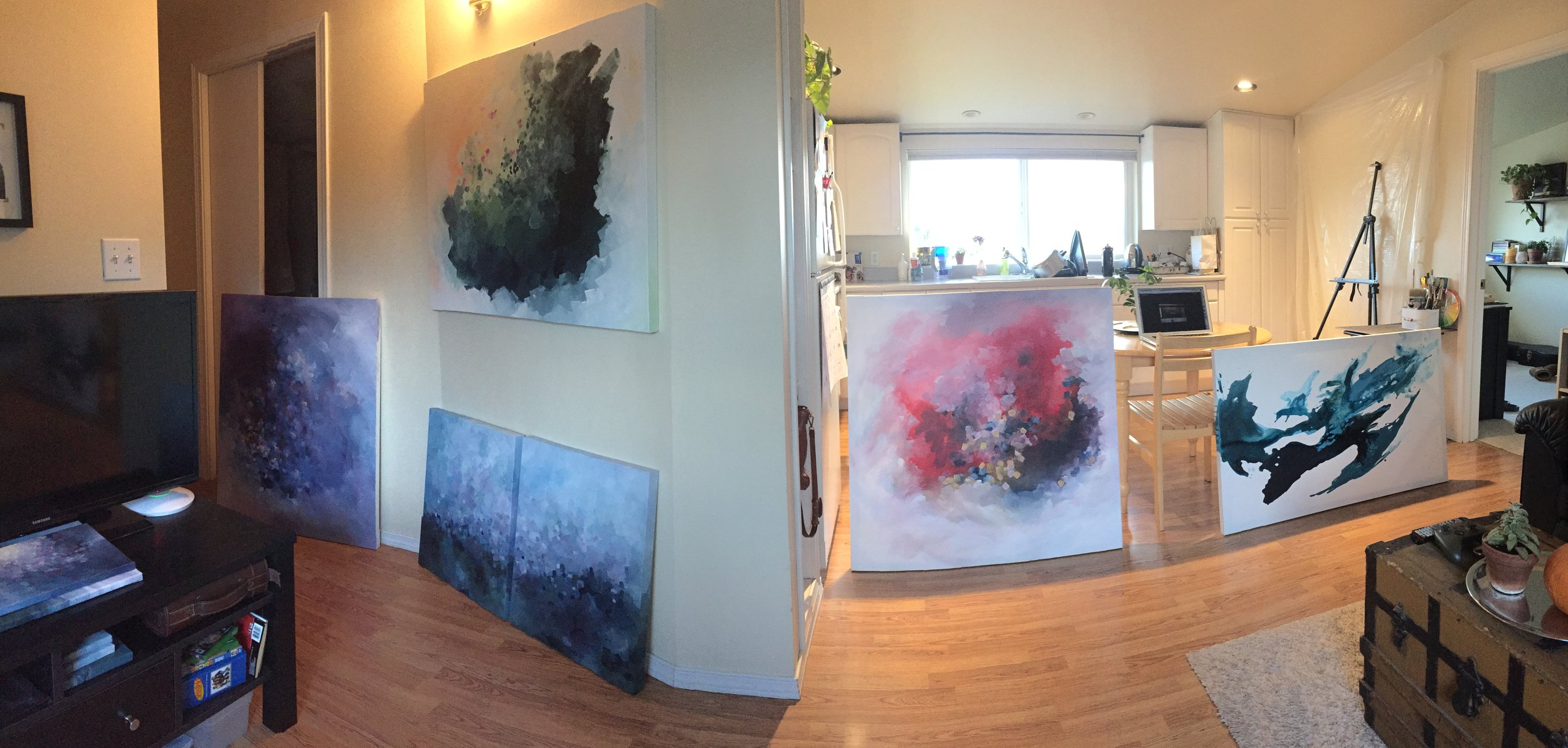Panoramic view, laying out artwork for a show in a one bedroom apartment. Kendra Castillo