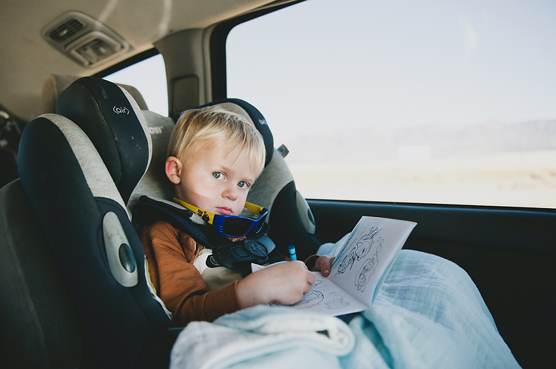 Little boy traveling in a car coloring in coloring book