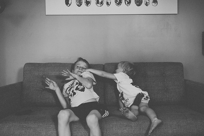 two boys playing on couch