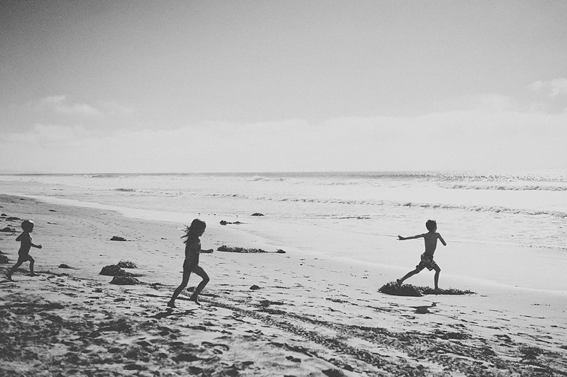 kids running on sand to the ocean