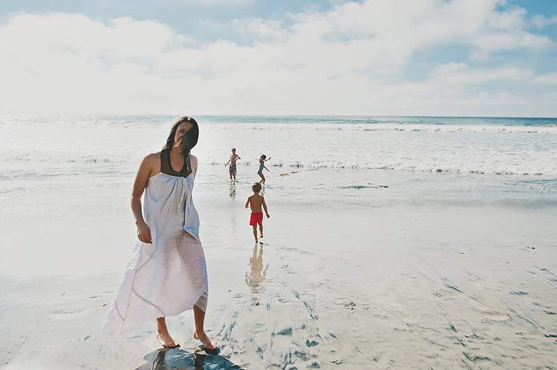 woman in dress on beach kids playing in ocean