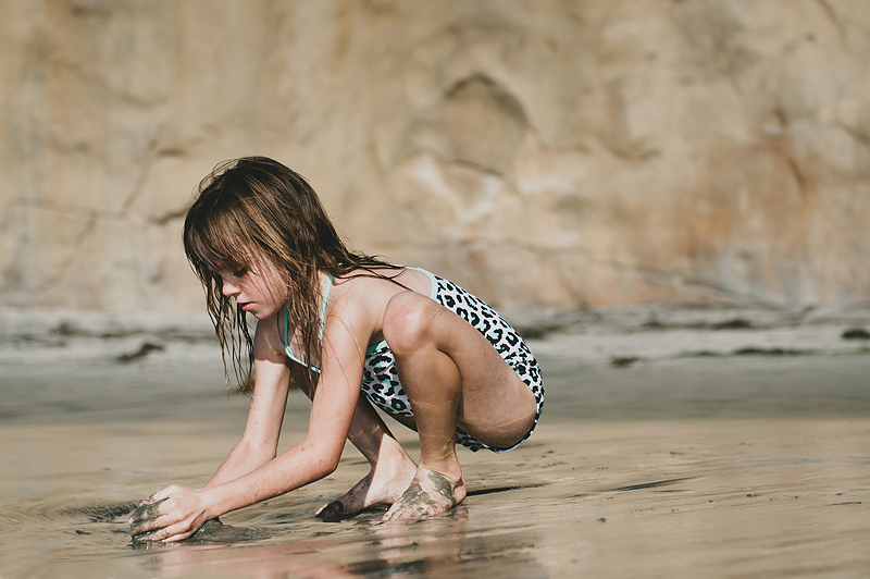 little girl playing in sand on California beach