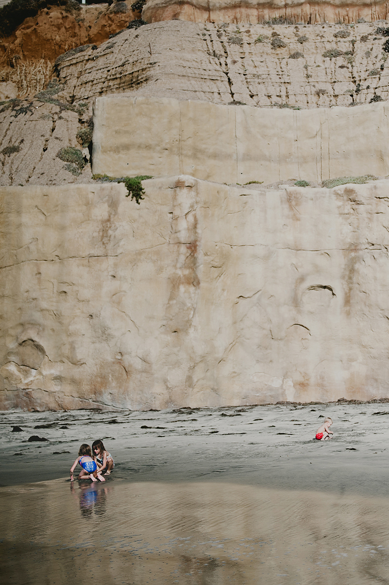 kids playing at base of cliff on california beach