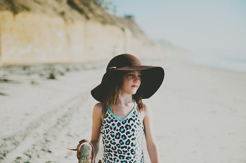 little girl wearing floppy hand on sandy California beach