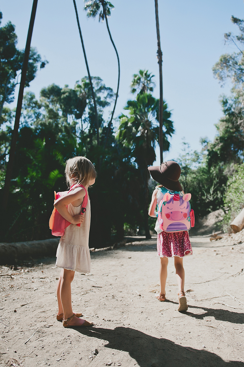 little girls wearing backpacks on dirt trail in California