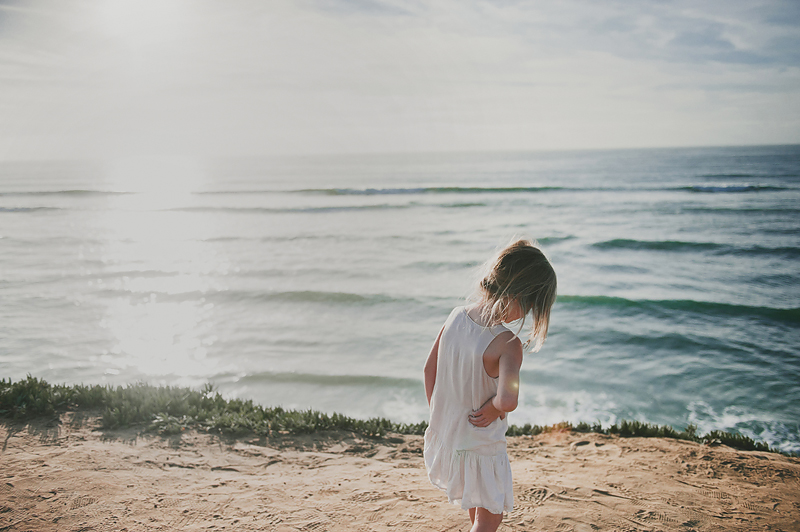 little girl standing on beach overlook in California