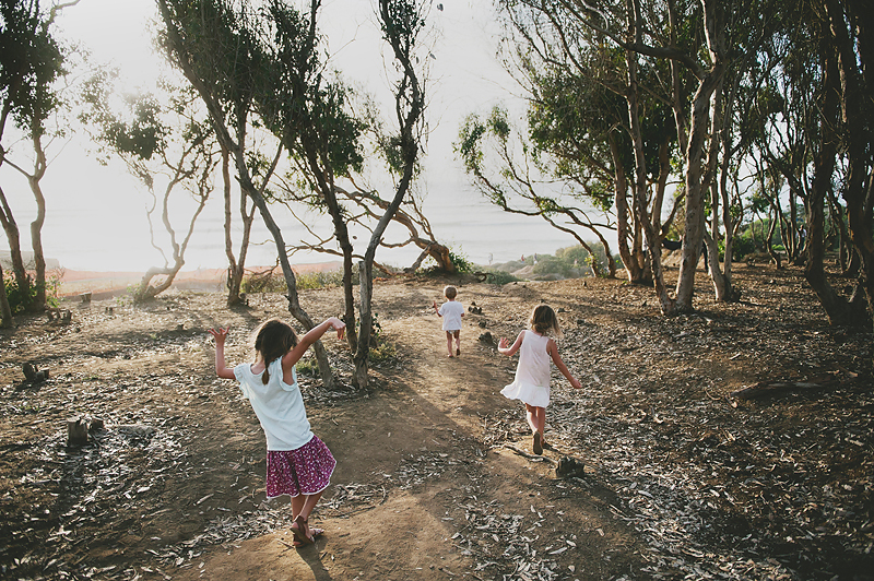 girls and boy walking on sandy path to ocean