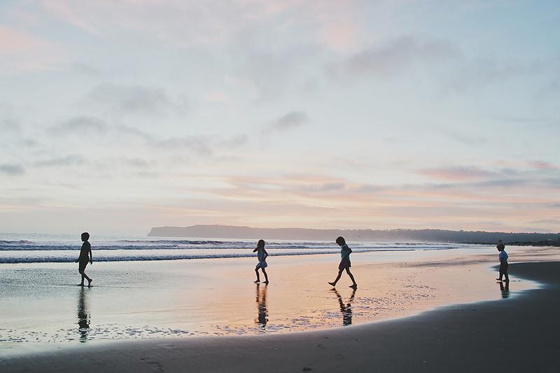 four kids walking on beach at sunset