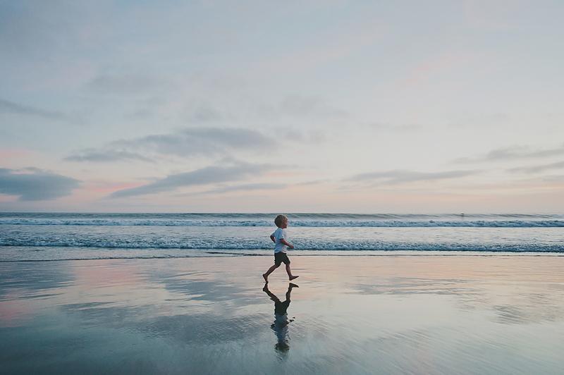 boy running on beach at sunset in california