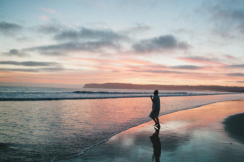 woman walking on beach in California at sunset