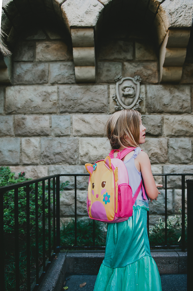 girl in princess costume waiting in line at Disneyland