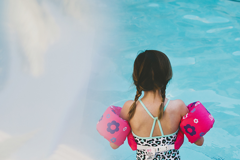 girl with braided pigtails wearing lifejacket in pool