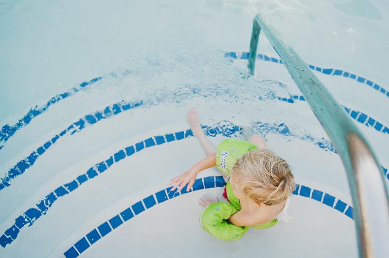 little boy sitting on steps of swimming pool in green lifejacket