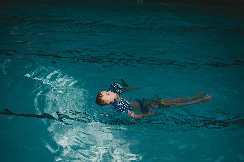 boy floating on back in swimming pool wearing shark floaties