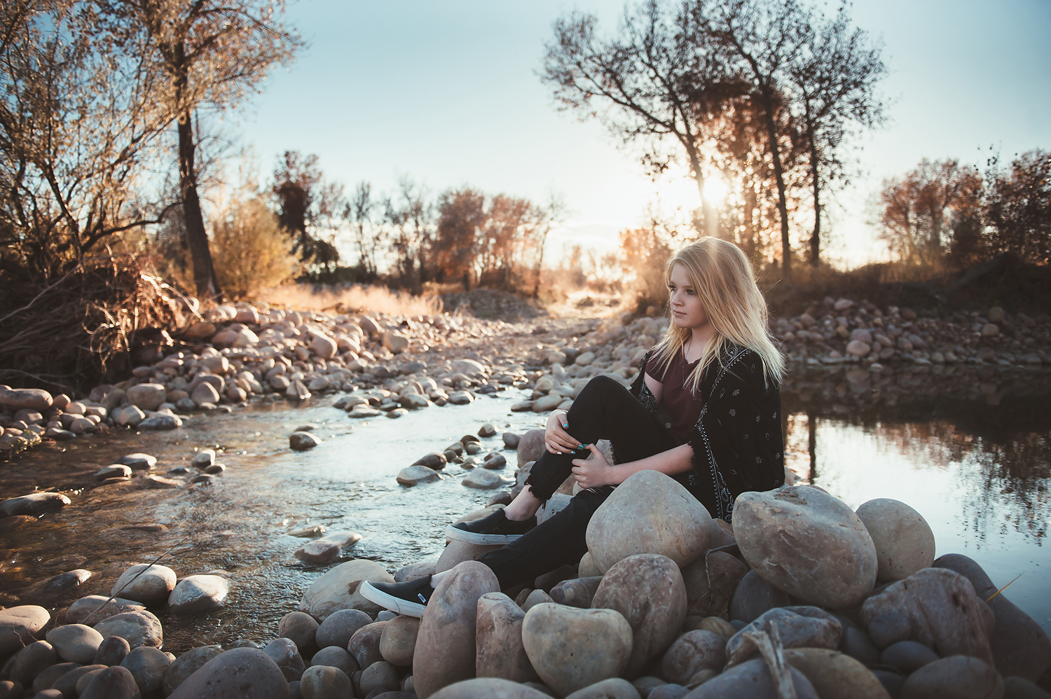 Girl sitting on rocks looking out over river