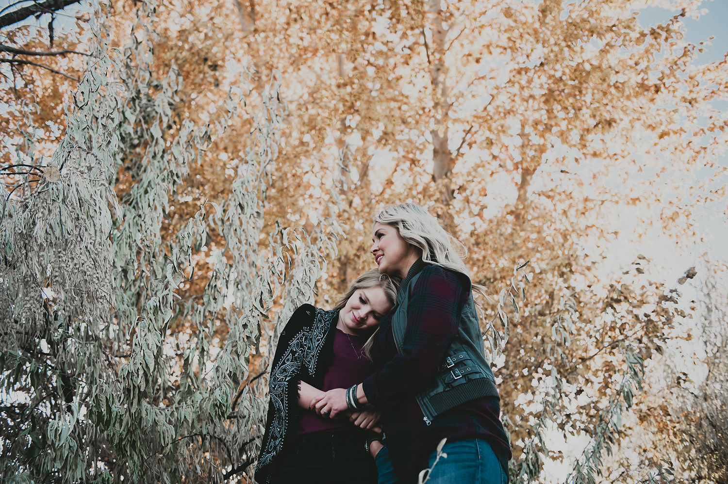 Mom and daughter hugging in front of yellow leaf trees