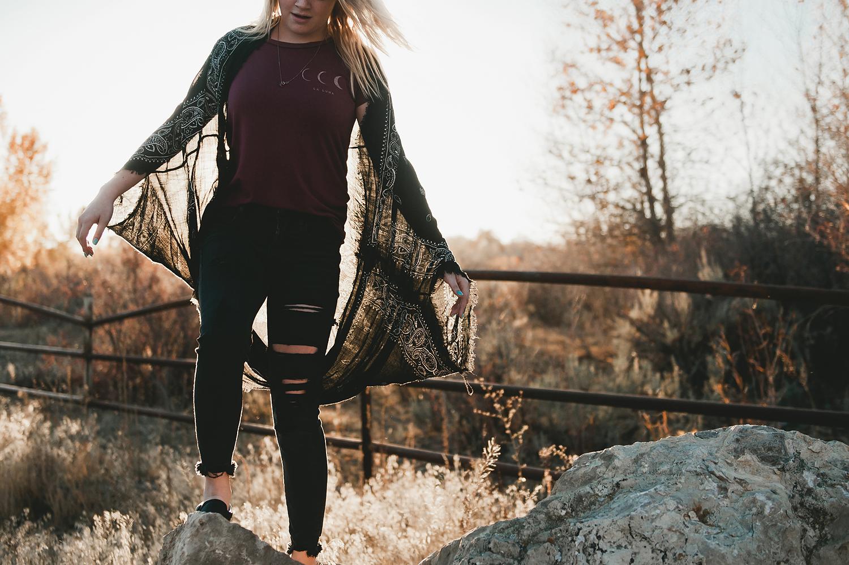 Girl in cardigan climbing around on rocks
