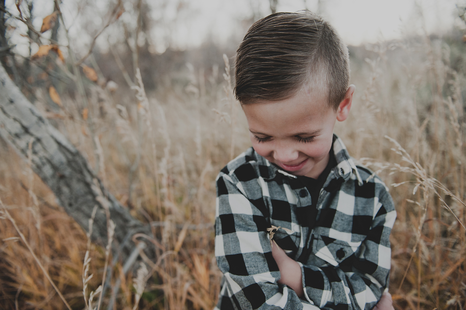 Little boy looking at ground laughing