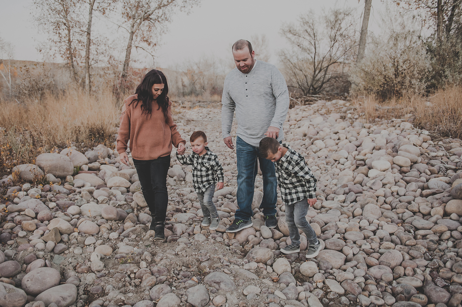 Mom and dad walking with kids on dry rocky riverbed