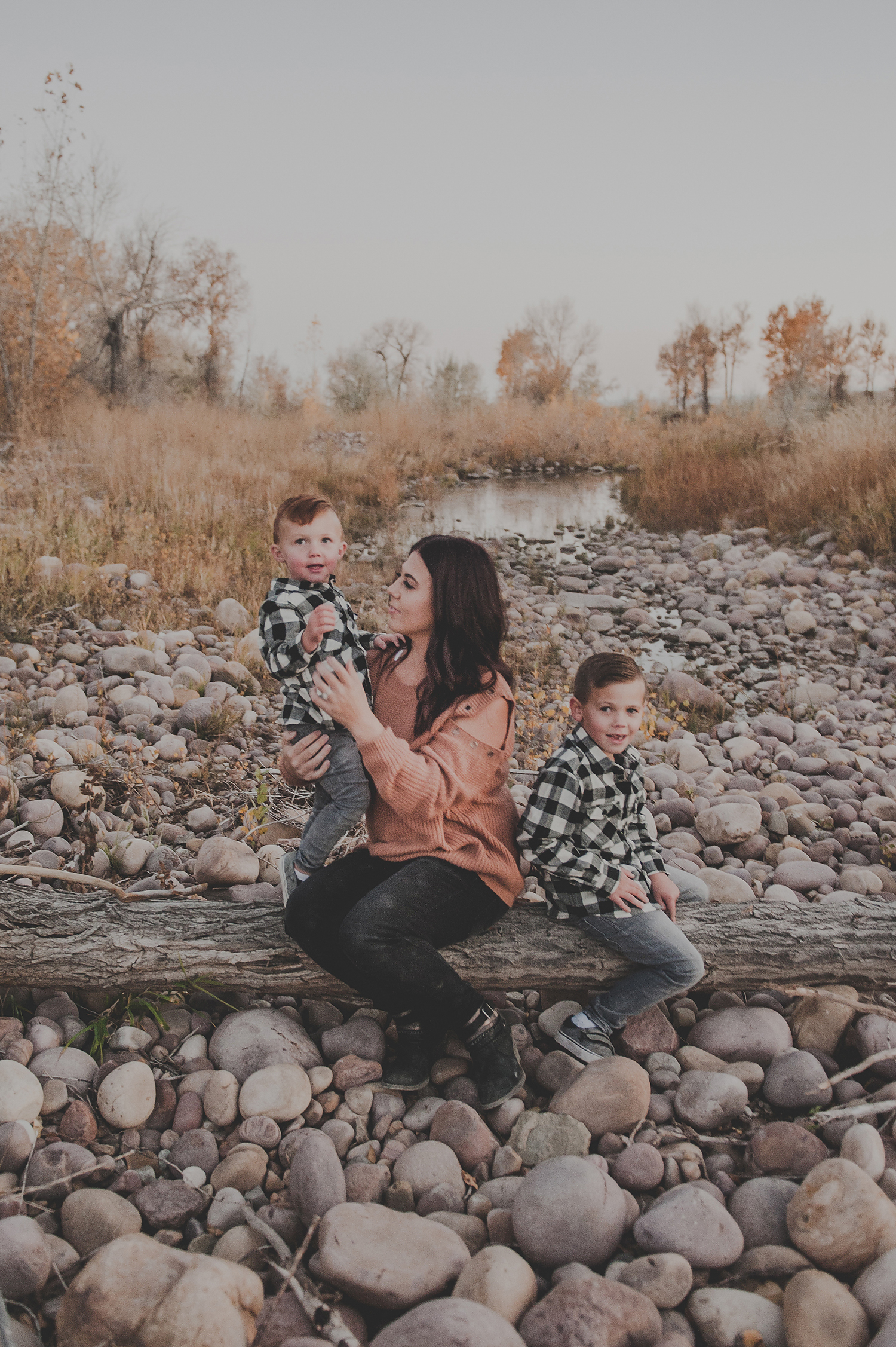 Mom sitting on log with kids