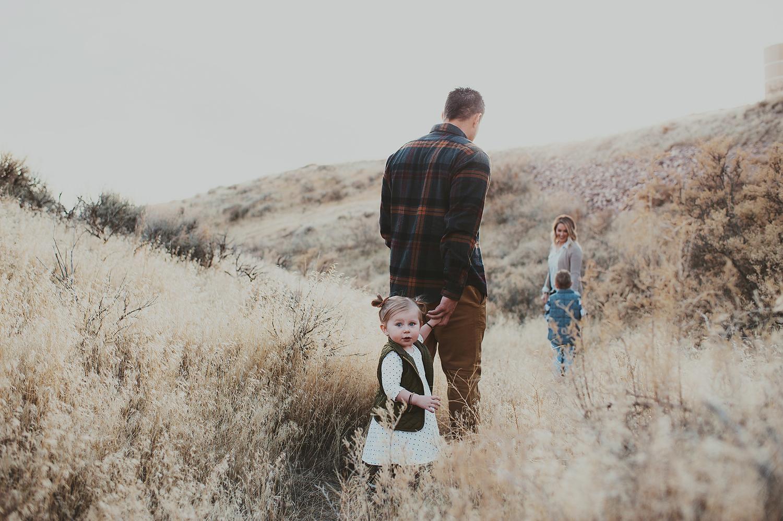 Family walking through golden grassy field