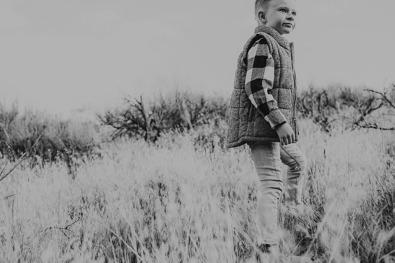 Little boy walking on grassy hillside