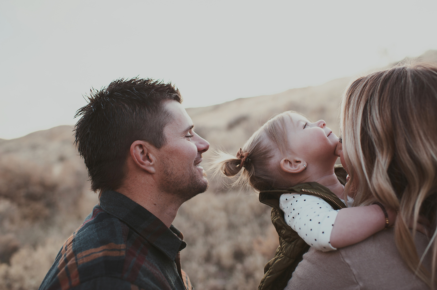 Mom and dad playing with little girl