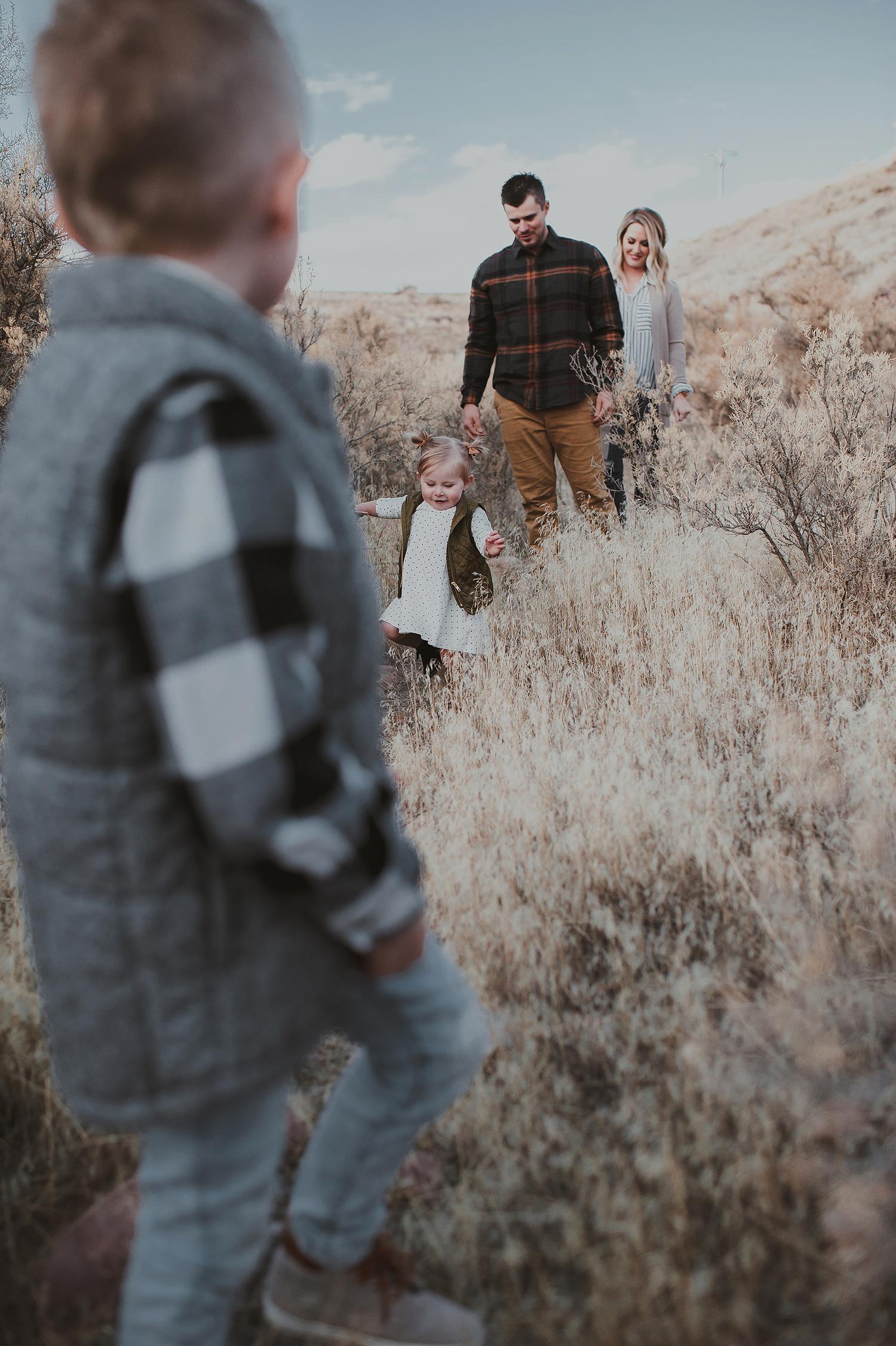 Family walking through grassy field