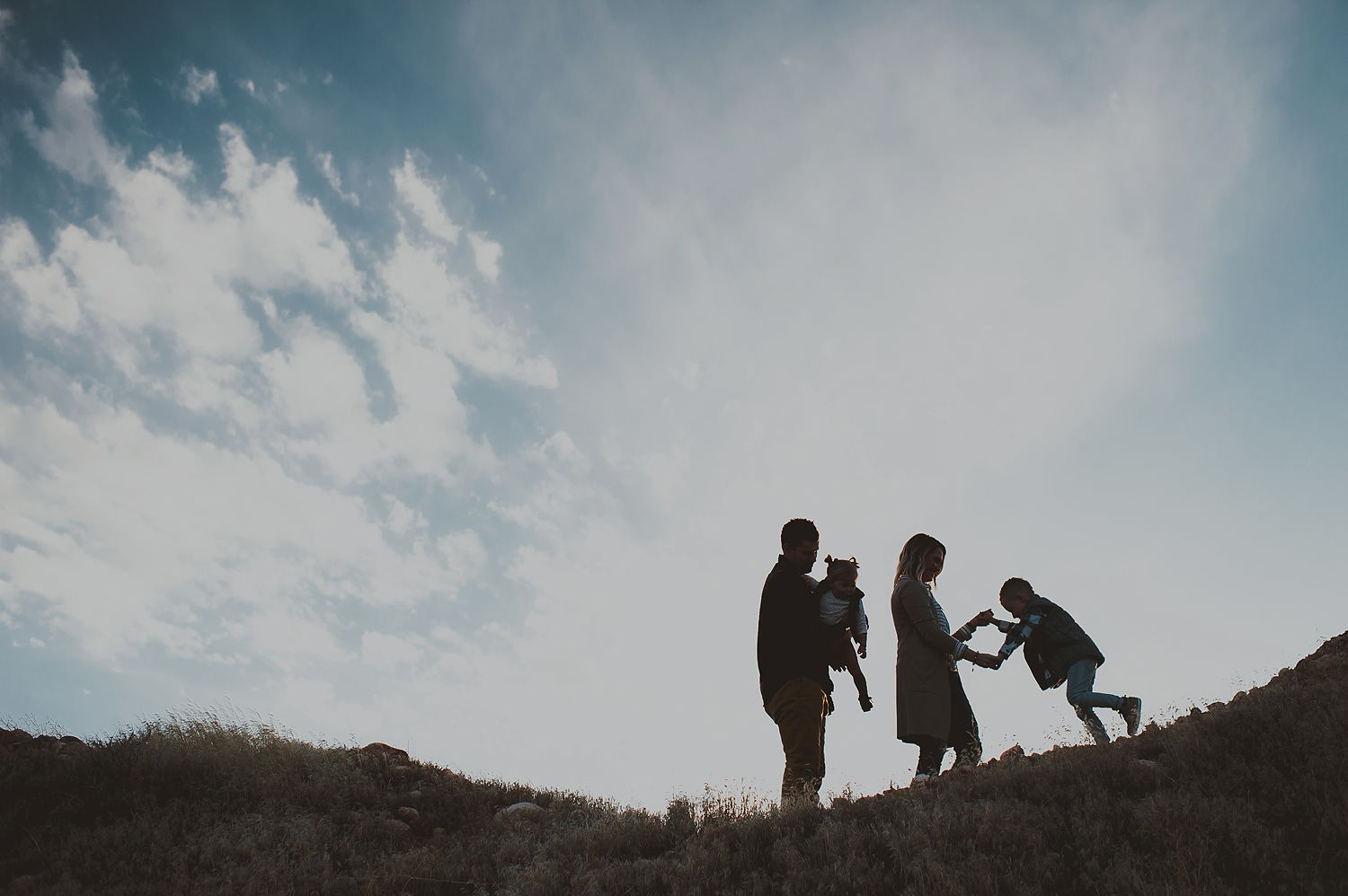 Family walking and playing on top of mountain
