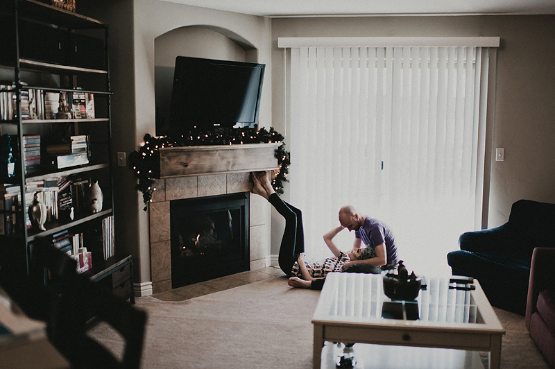 Couple snuggling on floor in front of fireplace