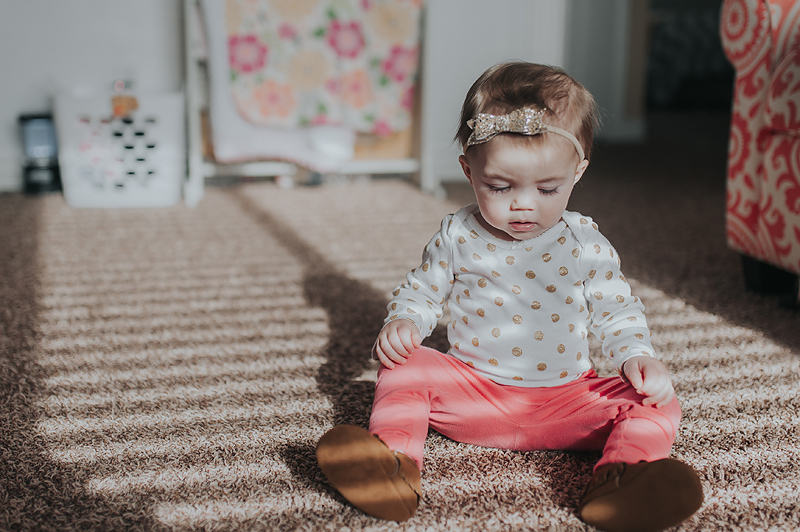 One year old girl in gold polka dot onesie in home