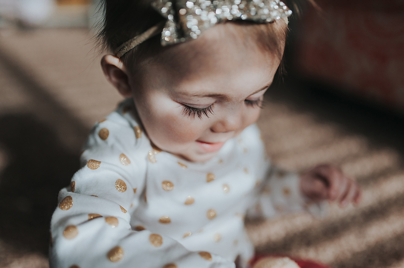 One year old girl close up of eyelashes and gold bow and gold polka dot onesie